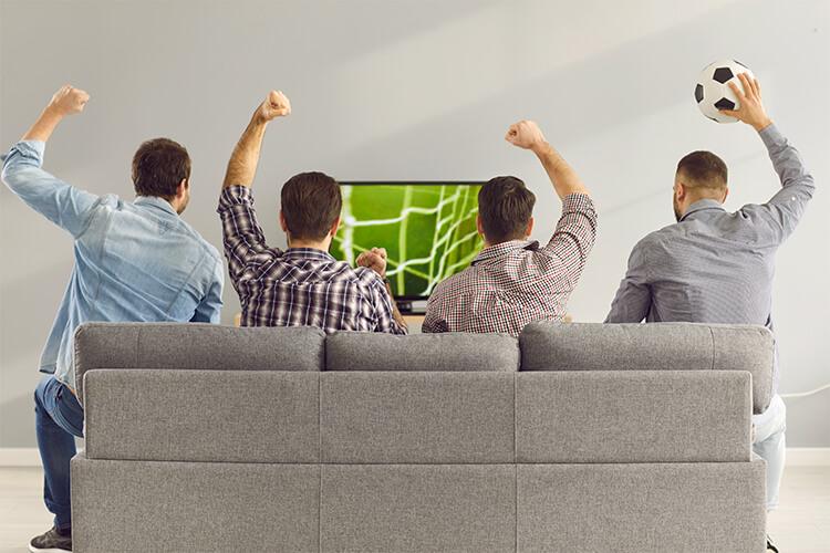 cinco-personas-festejando-con-las-manos-en-alto-en-una-mesa-redonda-con-dos-computadoras-papeles-y-3-vasos-de-agua-cuatro-hombres-festejando