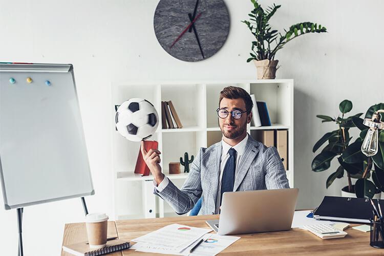 hombre-apostando-futbol-en-su-computadora-de-la-oficina-con-una-pelota-en-la-mano-computadora-oficina-escritorio-pelota-de-futbol-repisa-de-trabajo-doble oportunidad