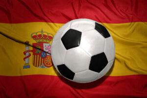 pelota-de-futbol-que-esta-sobre-la-bandera-de-espana-bandera-de-espana-flameando-pelota-de-futbol