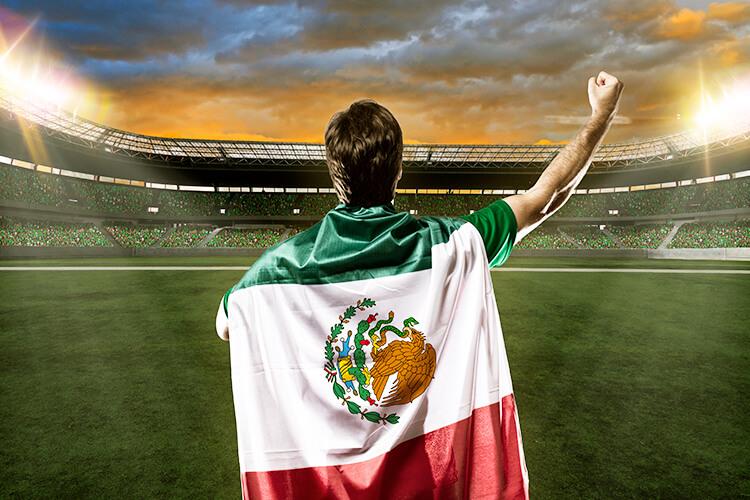 hombre-alentando-a-la-seleccion-mexicana-en-estadio-de-futbol-con-la-bandera-en-su-espalda-bandera-de-mexico-soccer-estadio-1.jpg